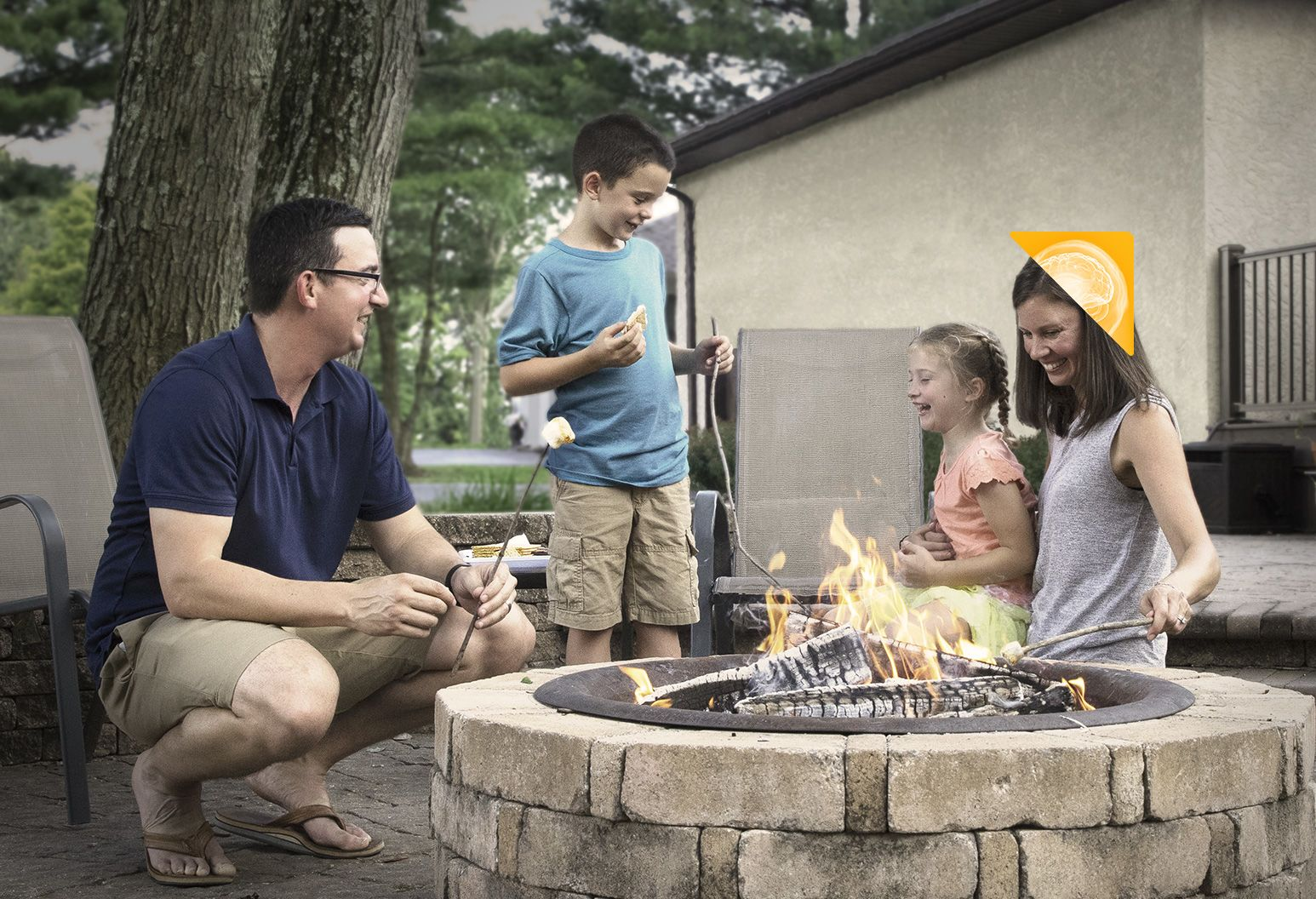 Kathy; an aneurysm survivor; and her family roasting smores outside of their home.