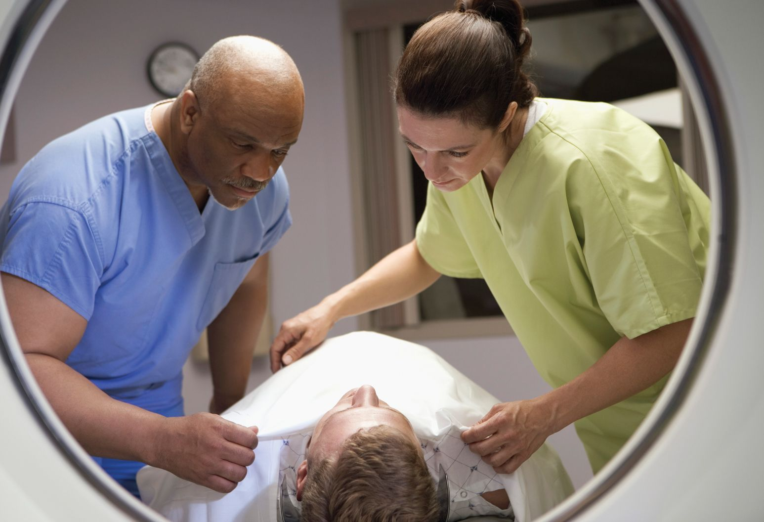 Two nurses in blue and yellow scrubs prepare a patient to receive imaging treatment