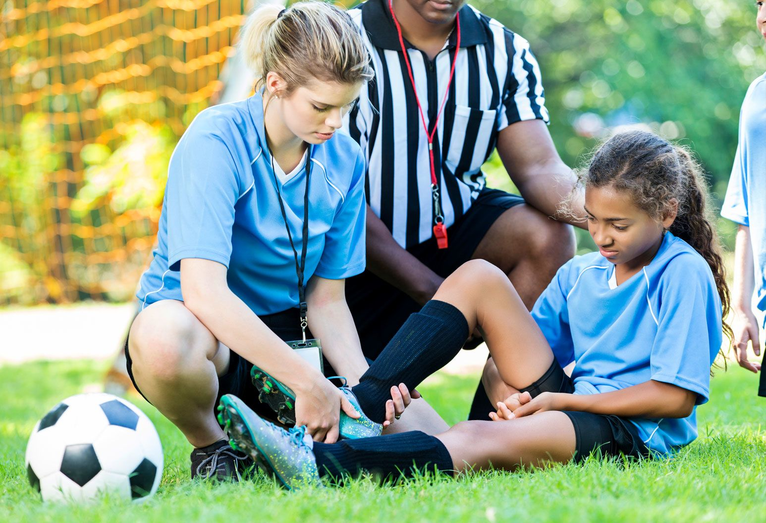 A young girl with an injured ankle sits on a soccer field. A woman is kneeling beside her, holding her ankle. A ref is also kneeling beside them.