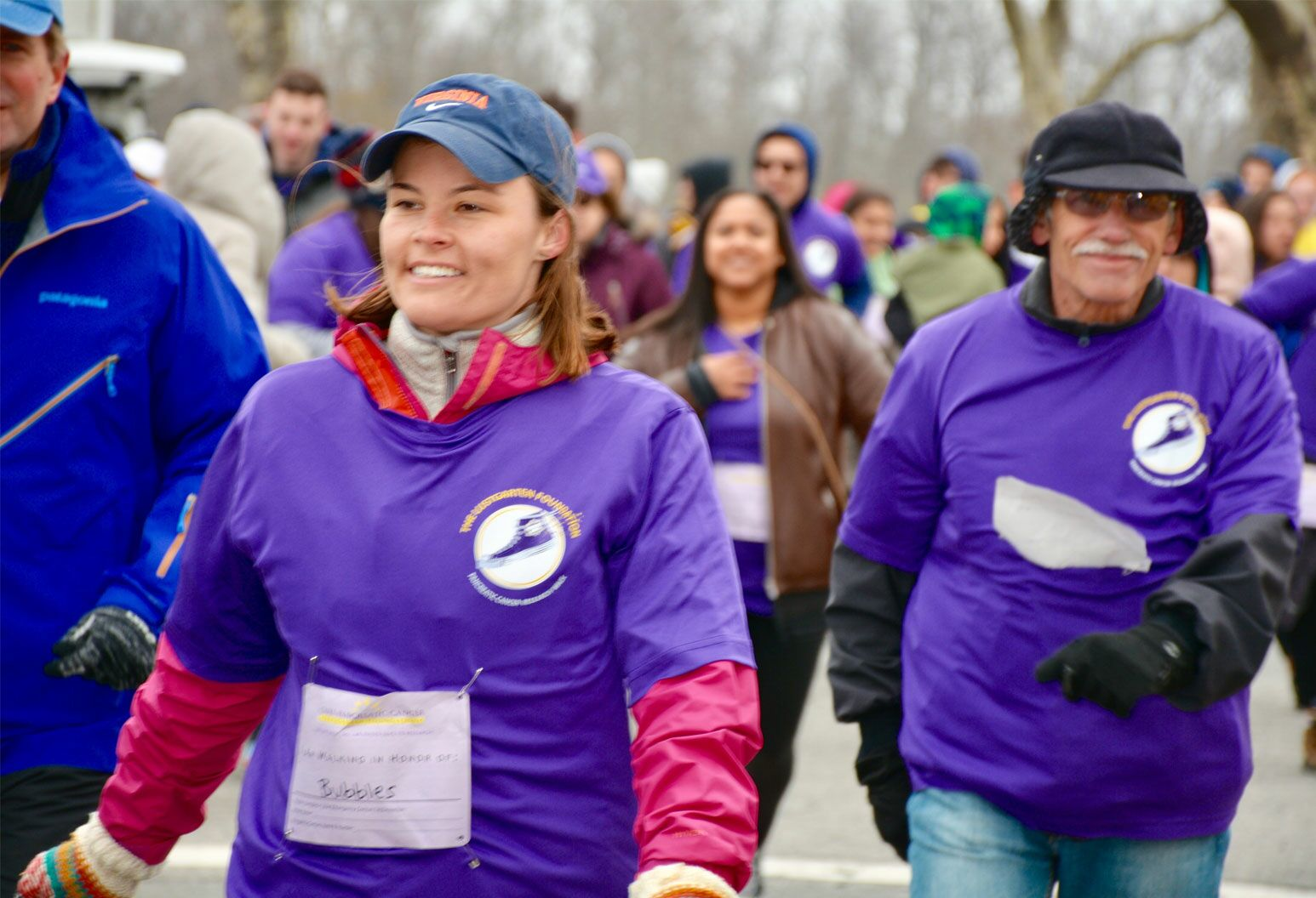 Group of people in purple shirts walking for an event