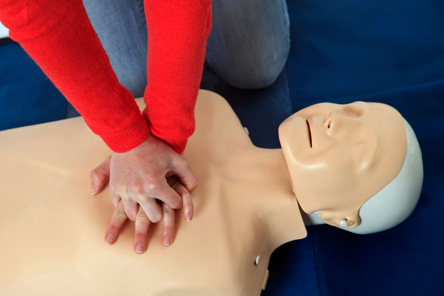 A persons trains on a CPR dummy
