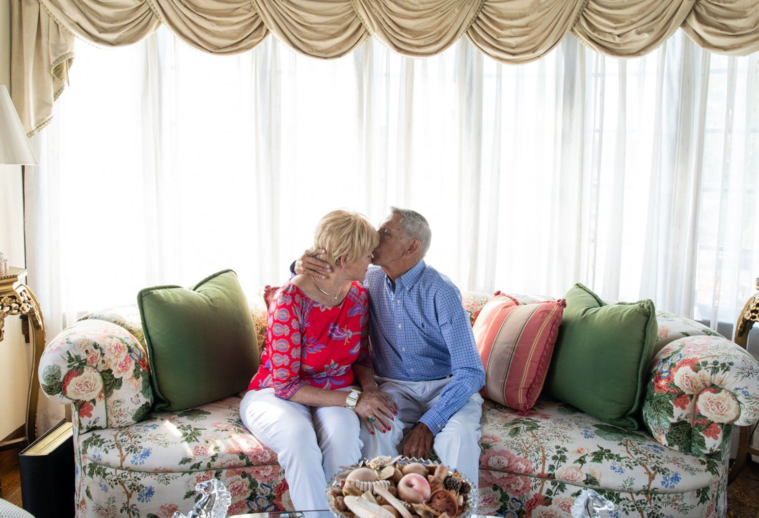 An elderly man kisses the forehead of an elderly woman as they sit on a couch in their lavish living room.
