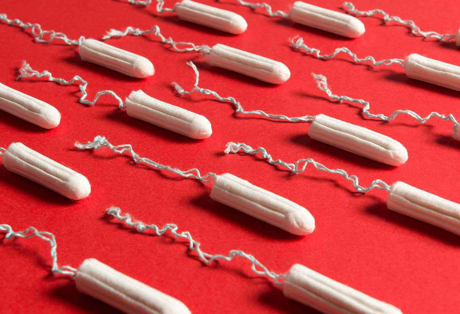 rows of white tampons laid over a red surface.
