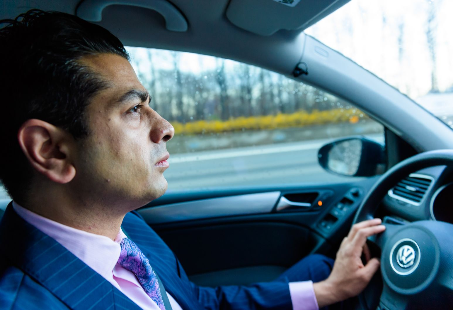 Man in striped blue suit, pink shirt, and purple graphic tie is focused on the road as he drives in his luxurious Volkswagon.