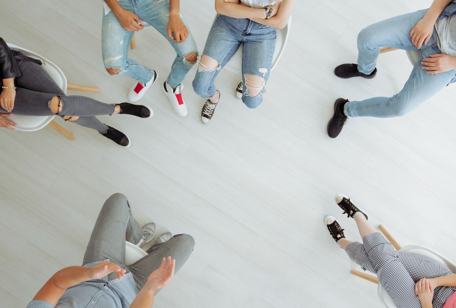 An overhead view of a group of individuals sitting in a talk circle. They are all wearing casual clothing.