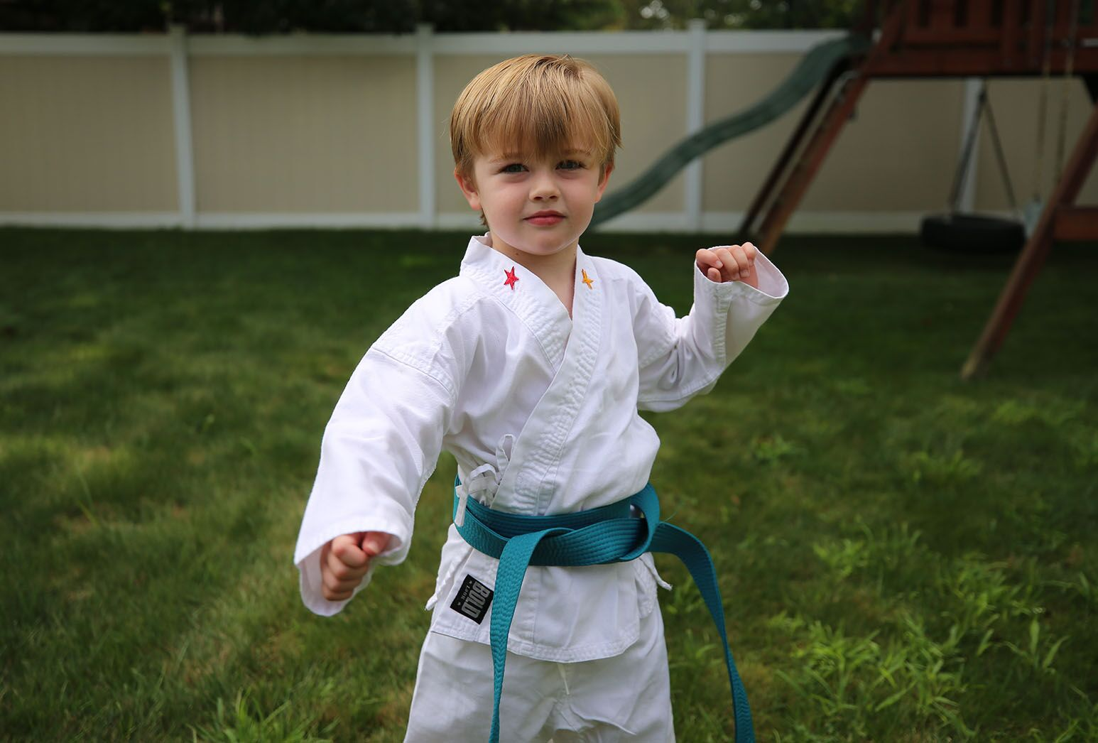 Young boy with blond hair practicing karate outside in a white karate uniform and green belt.