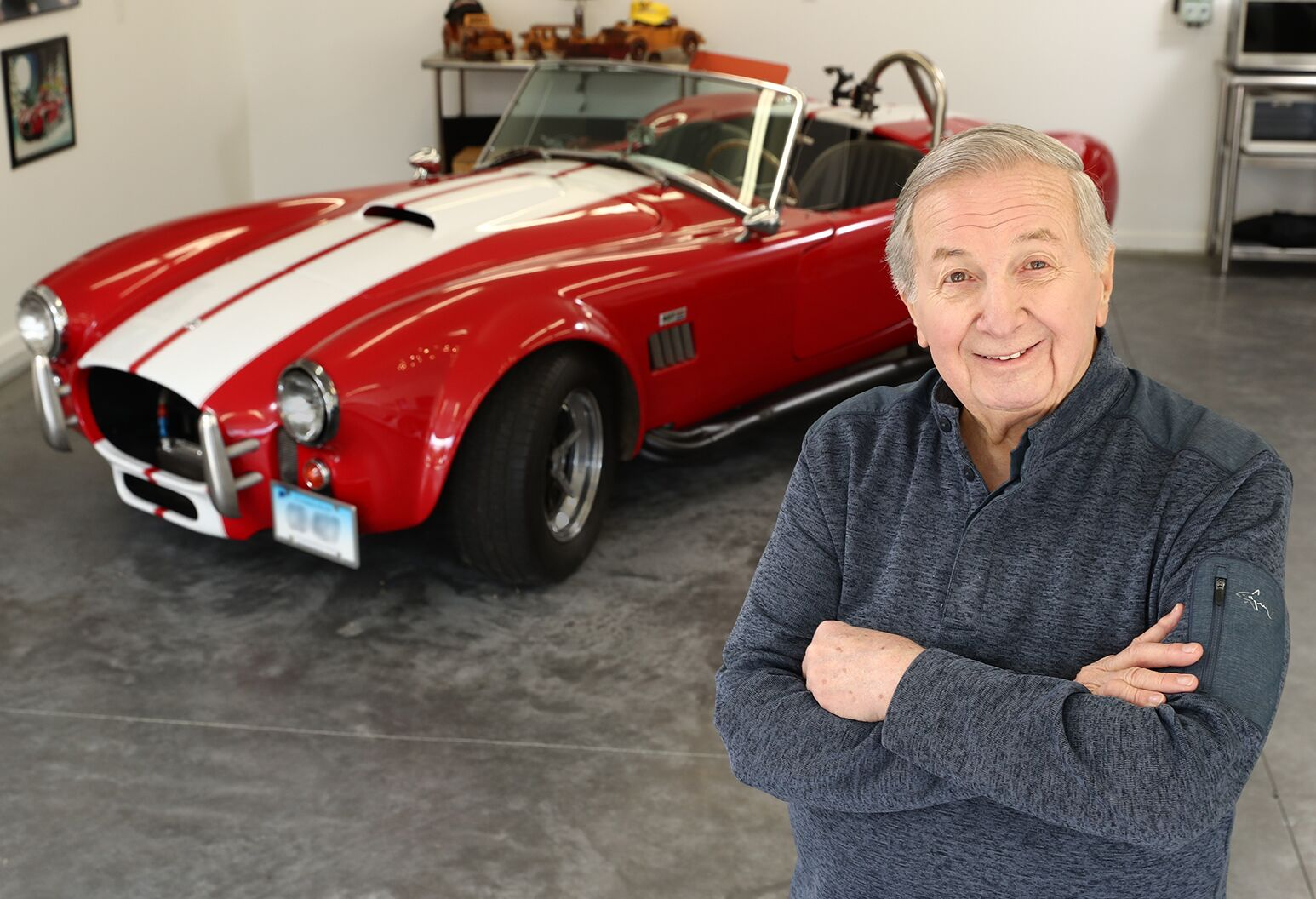 Smiling man in his 70s in his garage, standing in front of a red hot rod.