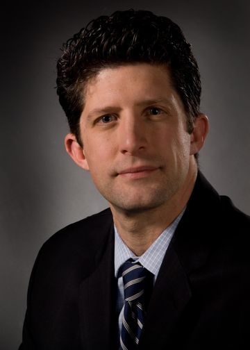 Joseph Schulman wearing a blue and grey tie