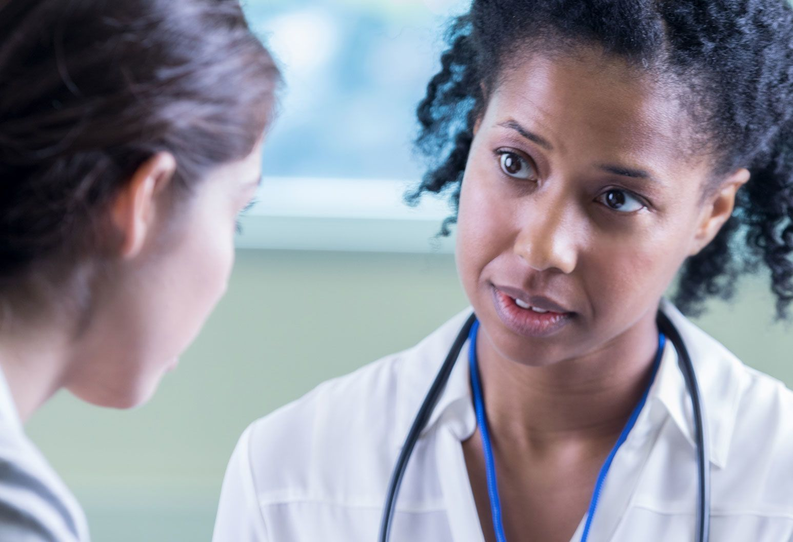 female physician looks sympathetic as she listens to patient