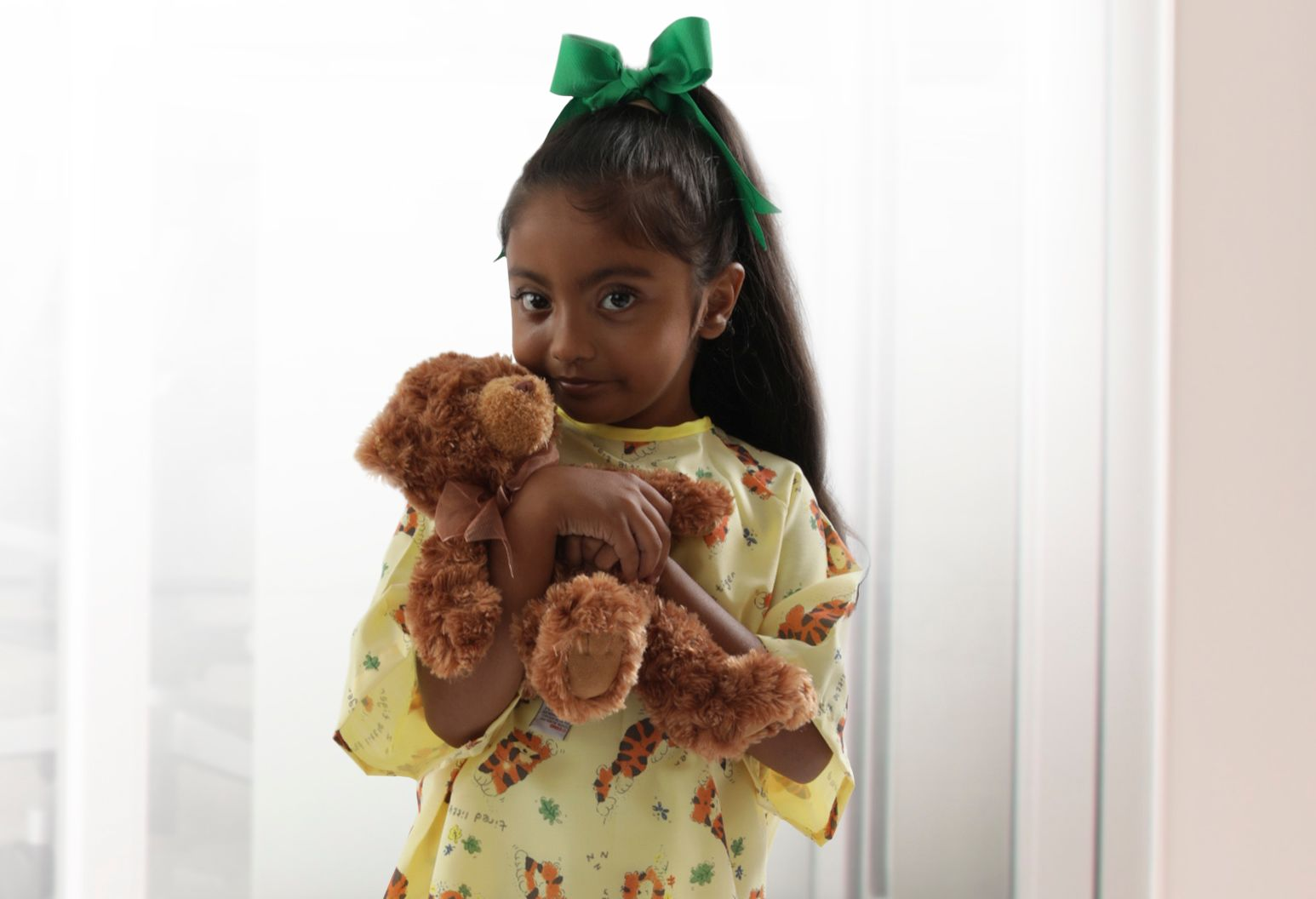 young girl wearing yellow pajamas has a green bow in her hair and is holding a teddy bear