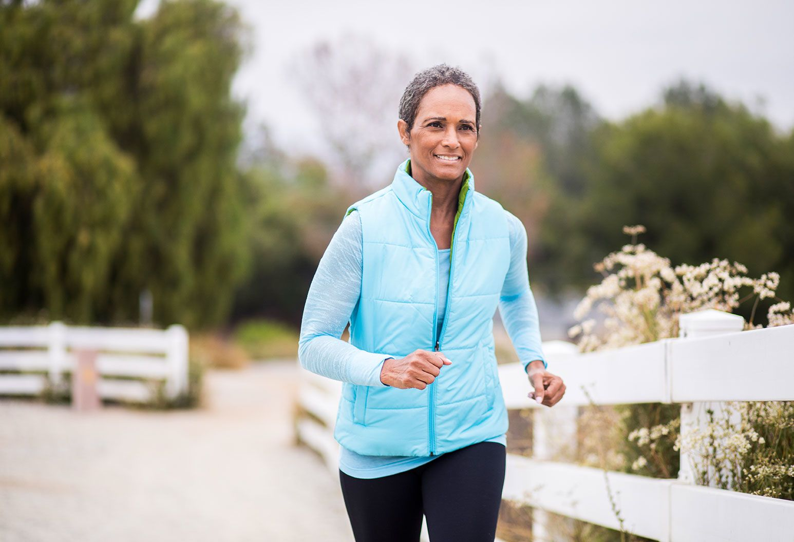 Elderly, dark-skinned woman with short hair jogs outdoors. She is wearing a blue sleeveless bubble vest with a light blue sweater under it. She looks like she is faintly smiling through the pain of jogging.