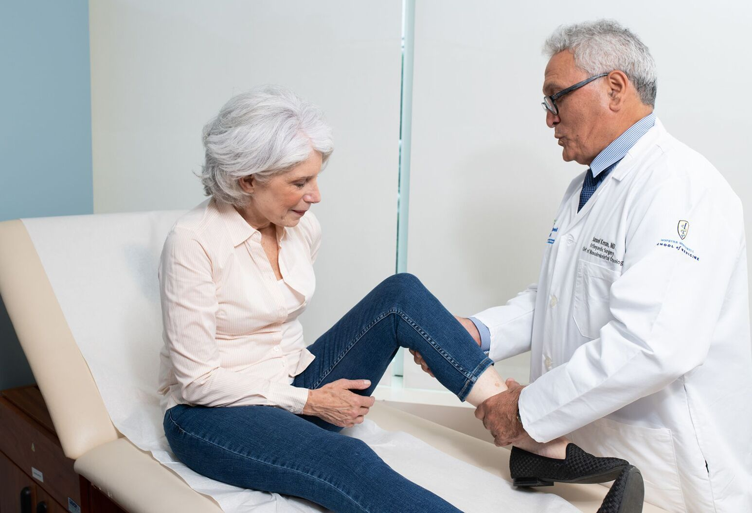 Elderly woman has her knee examined by a doctor
