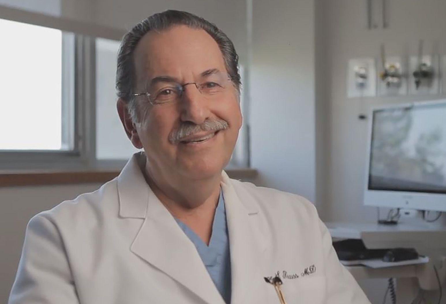 Dr. Euegene Krauss wears scrubs and a white lab coat and smiles at the camera. He has gray hair and a mustache and wears glasses without frames.