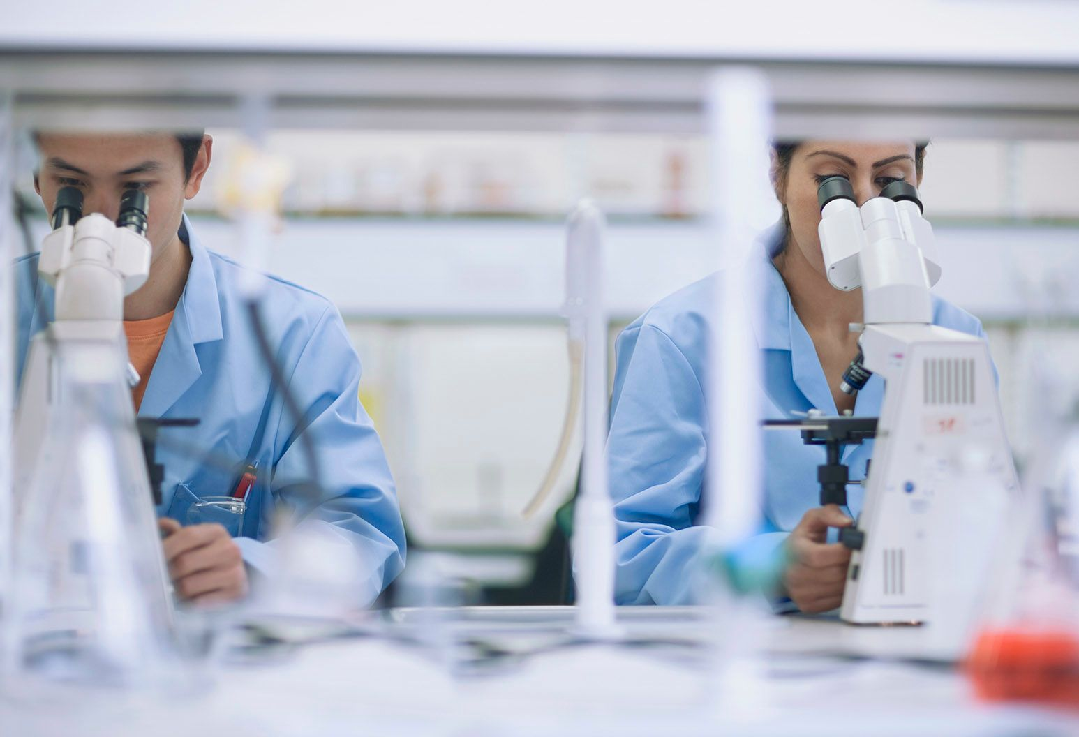 Two researchers wearing blue coats sit side by side and look into microscopes.