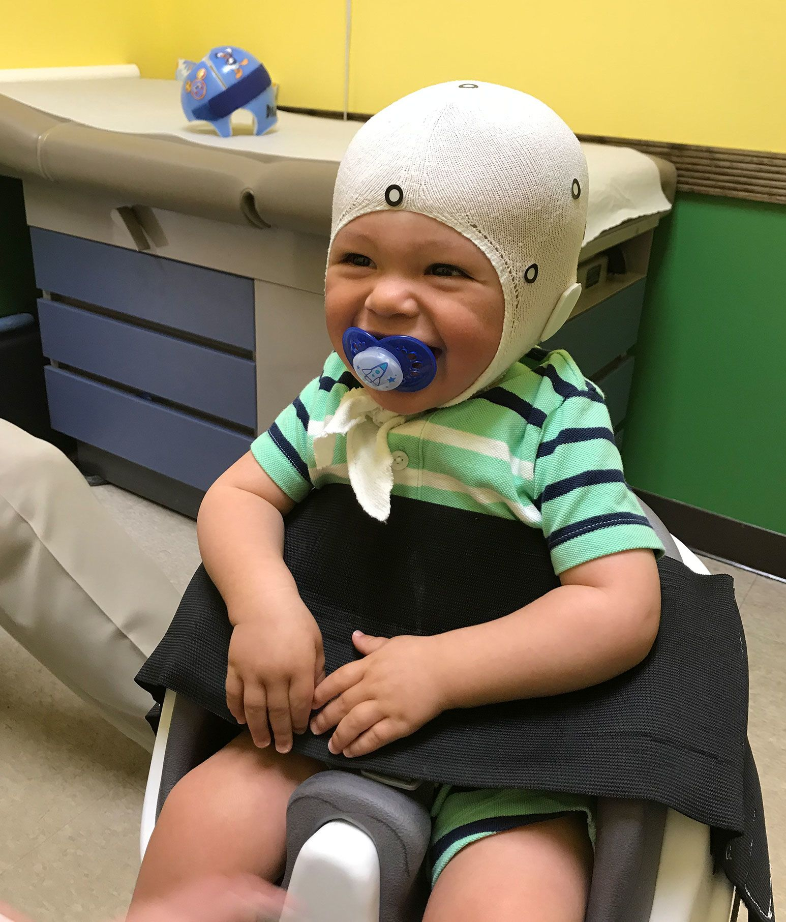 A baby sits on a white chair with a black strap over him. The baby is smiling as he holds a pacifier in his mouth and wears a white cap over his head.