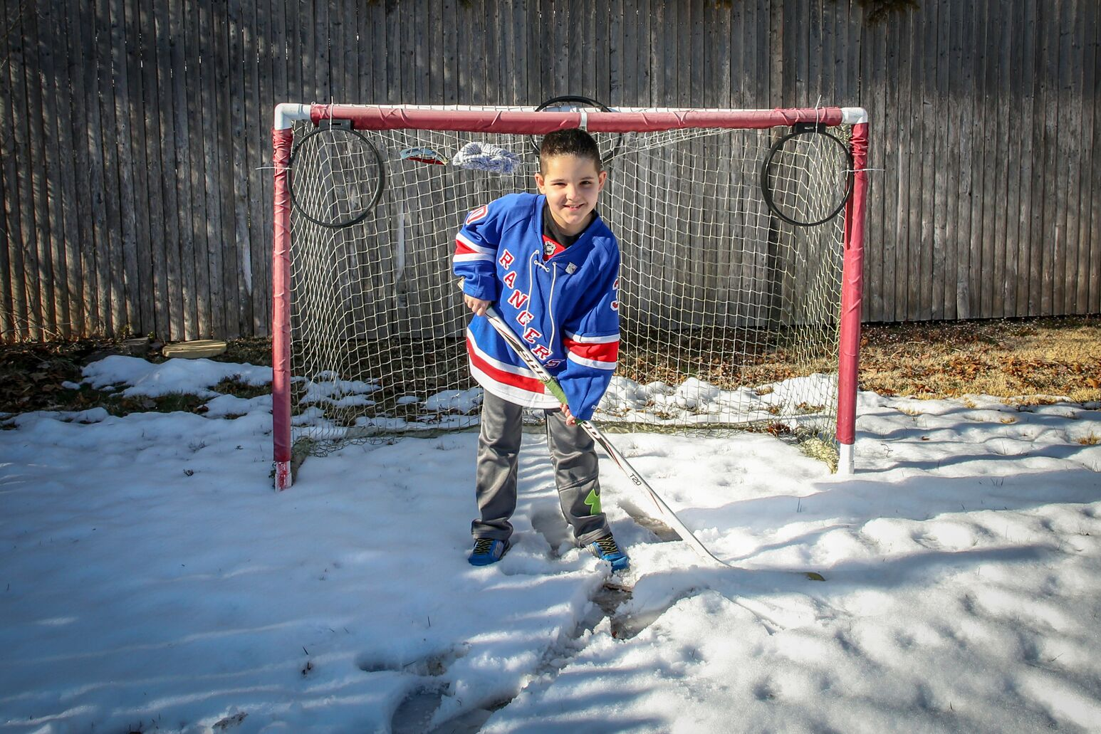 John Higgins wearing a Rangers jersey and playing hockey in the snow.