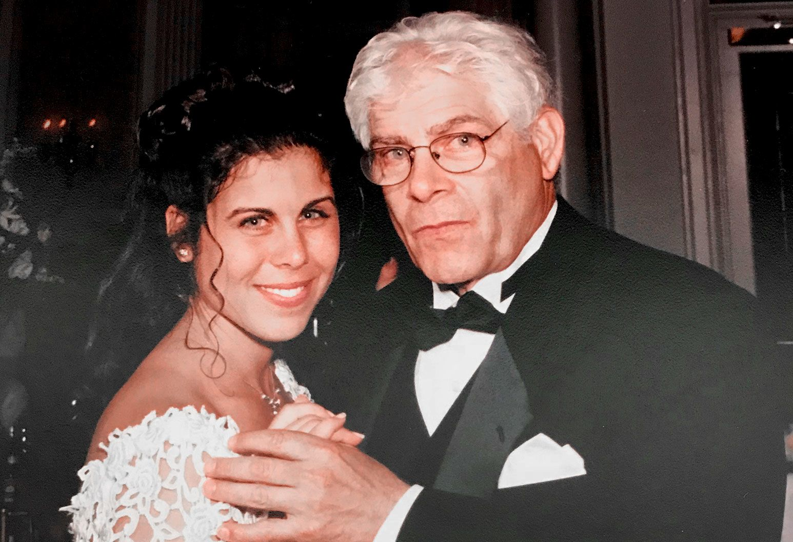A Woman with black hair in a wedding dress smiles at the camera as she dances with an older man with gray hair and glasses in a tuxedo.