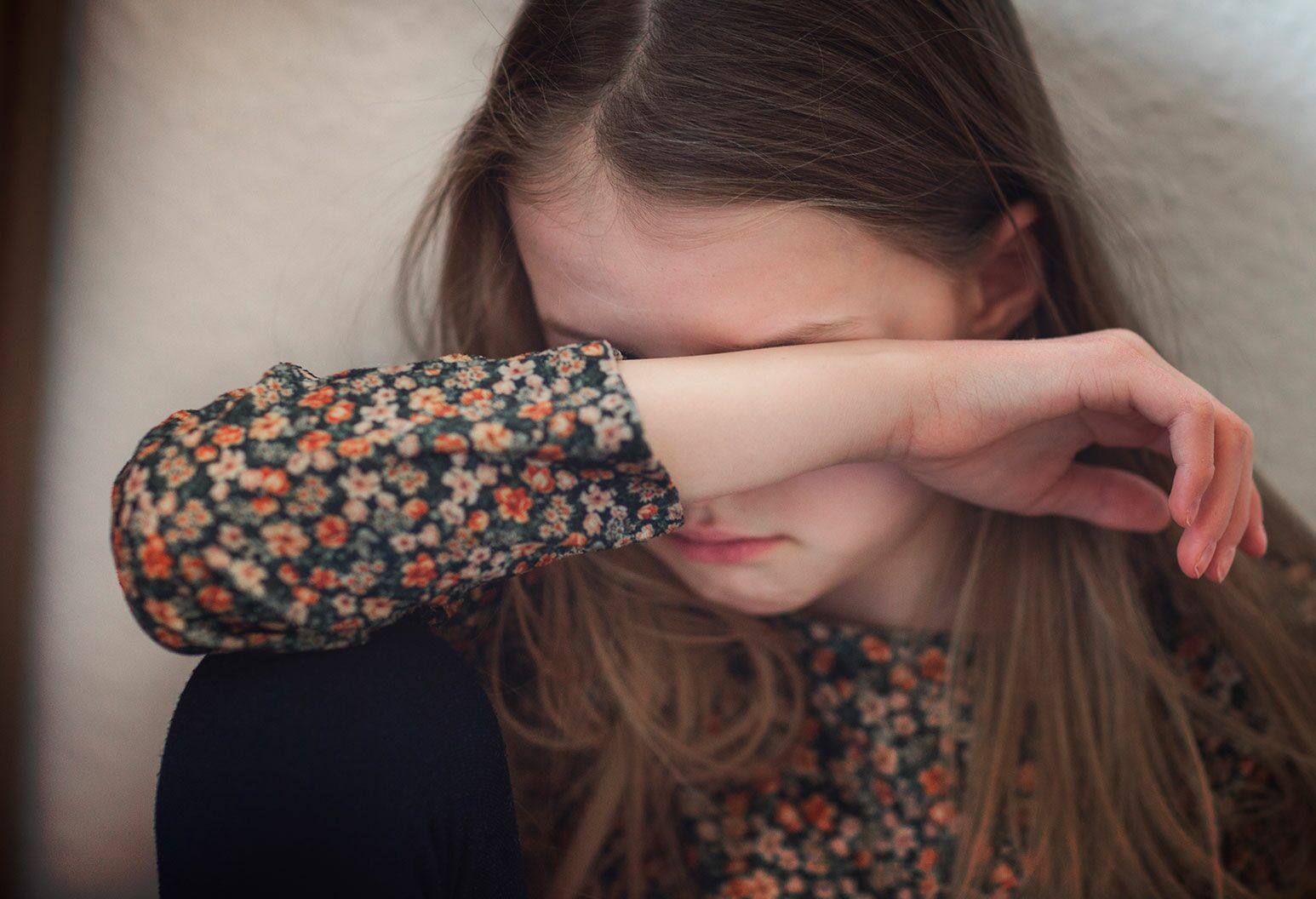 A young girl in a floral blouse and black pants sits against the wall wiping her face with her forearm.