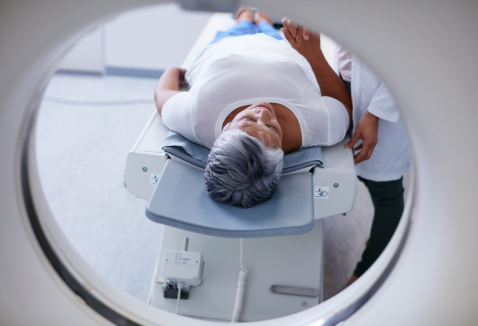 Woman with short gray hair on scan machine being comforted by a doctor