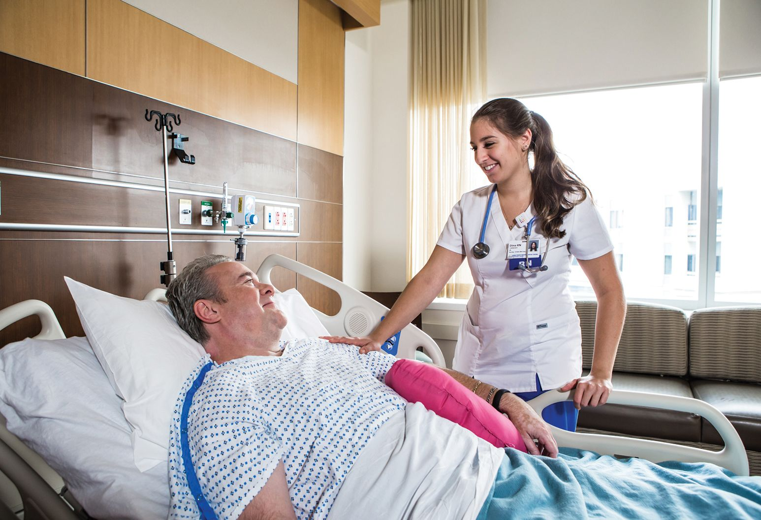 A middle aged man is laying in a hospital bed looking at a young female nurse, who is standing bedside. She touches his arm and smiles at him.