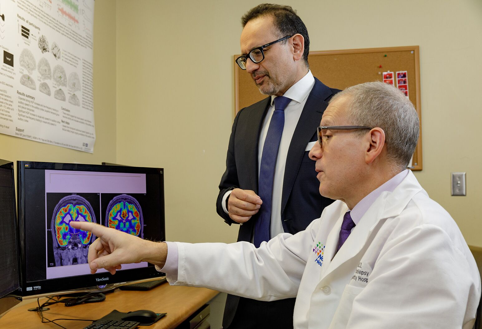 two physicians looking at a brain scan on a monitor