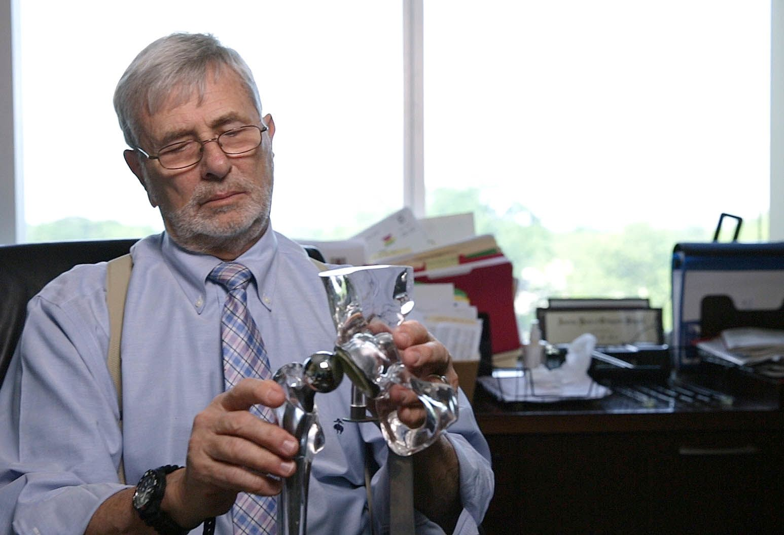 An older man with gray hair, blue shirt, striped tie, and beige suspenders sits in his office playing with a model of a hip bone.