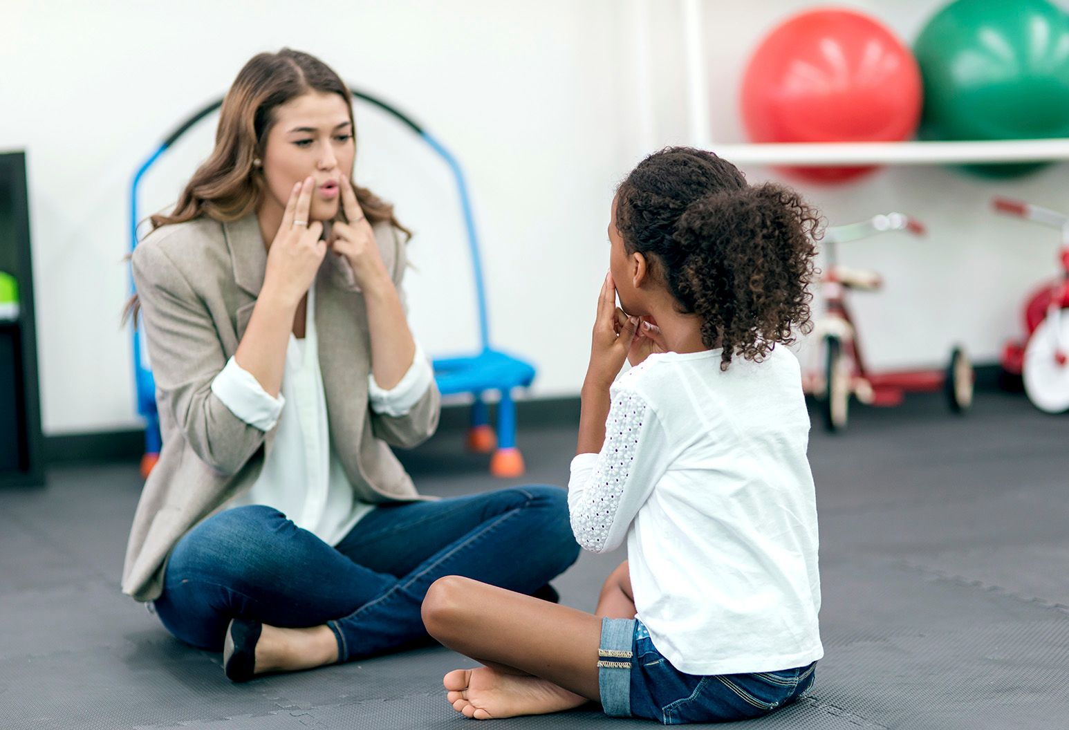 An adult female therapist guides a young girl in speech therapy for a therapy exercise. They're sitting cross-legged on the floor.