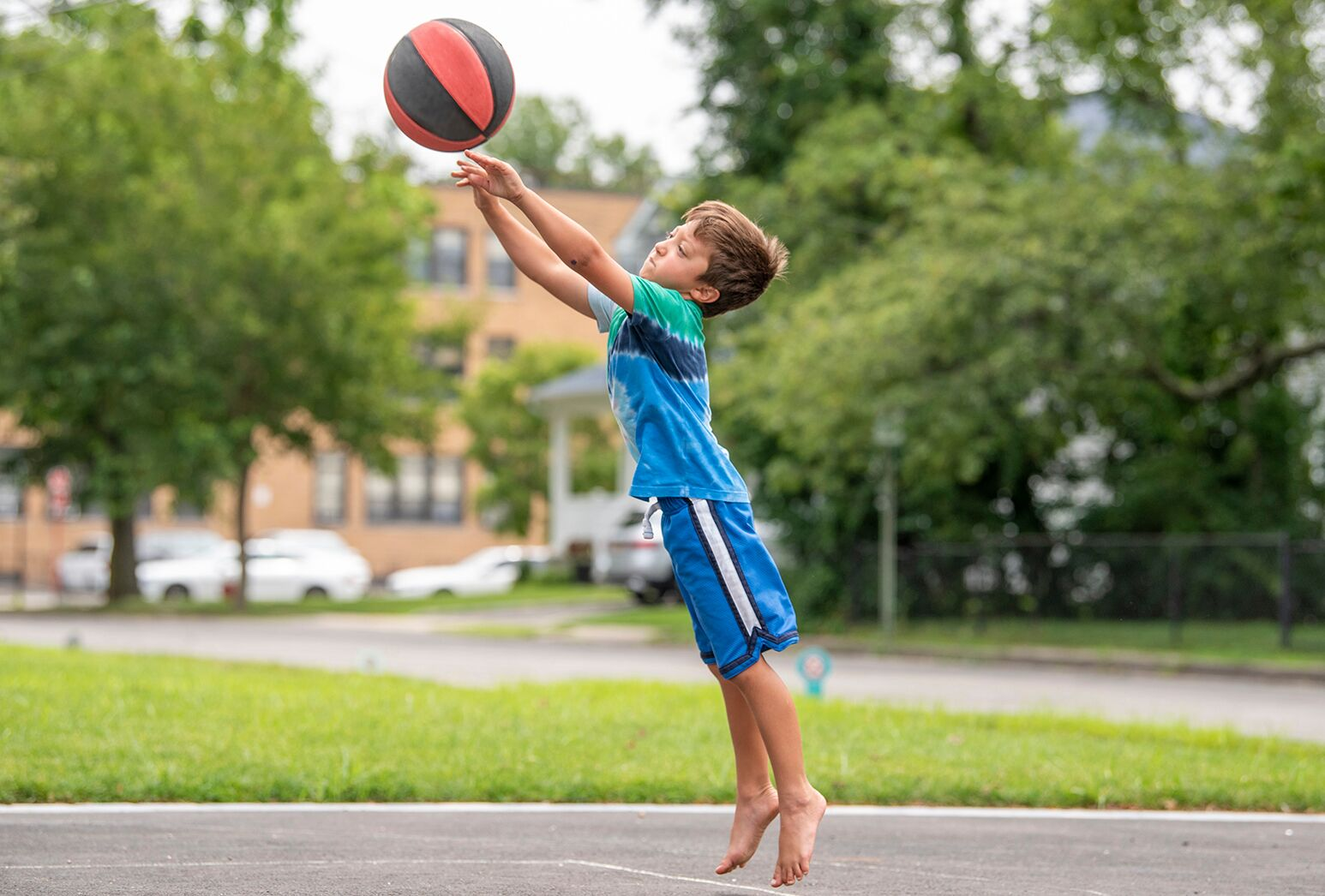 Barefoot little boy in blue shorts and top shooting a basketball.