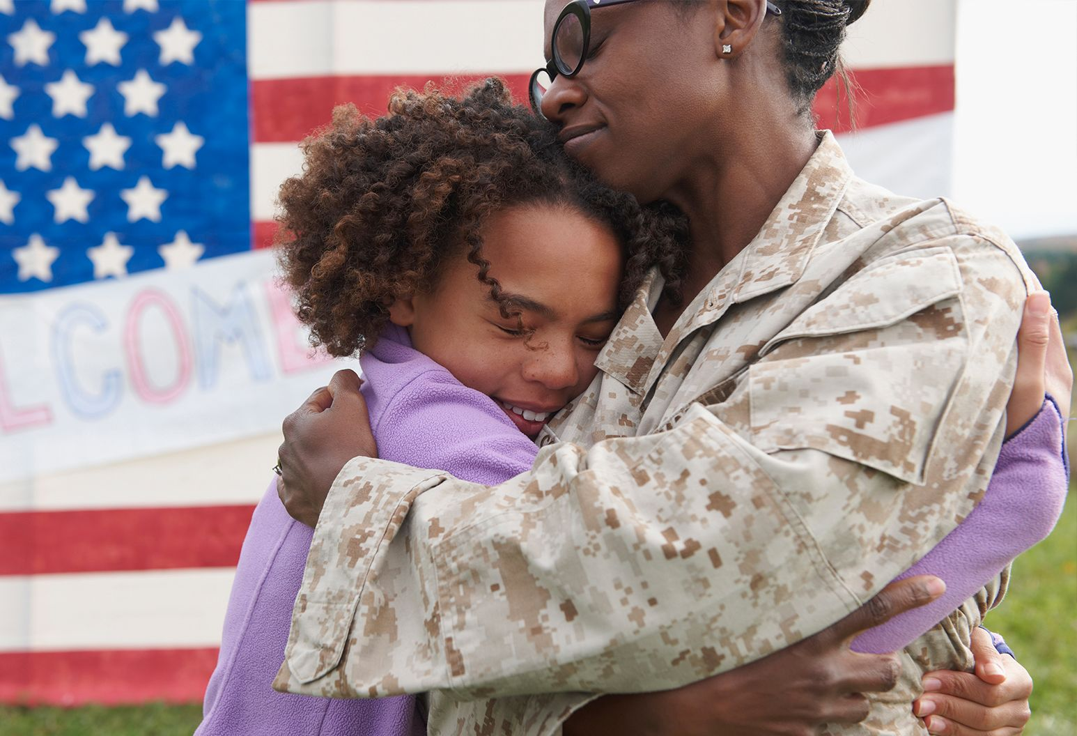Servicewoman in camouflage is hugging young girl in purple shirt. American flag is in background with welcome home sign.
