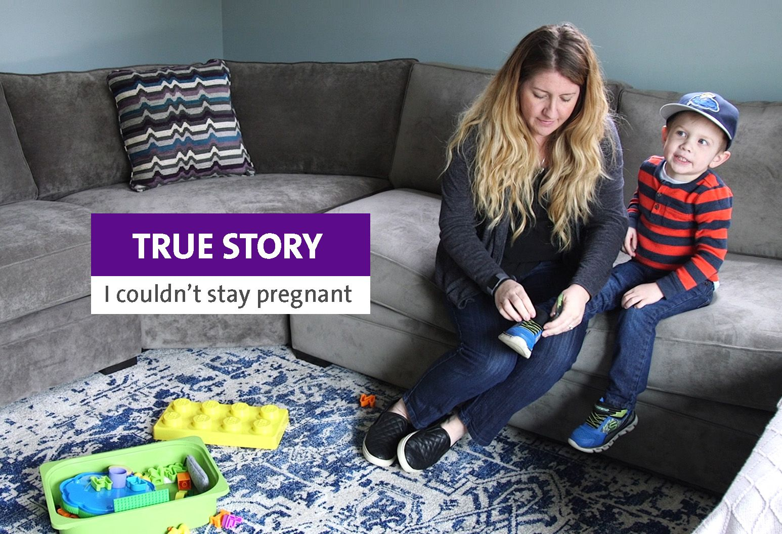 A woman with long blond hair is tying the shoe os a young boy wearing a blue baseball cap and stripped shirt. They are sitting ona  gray couch and there are toys on the blue and white rug.