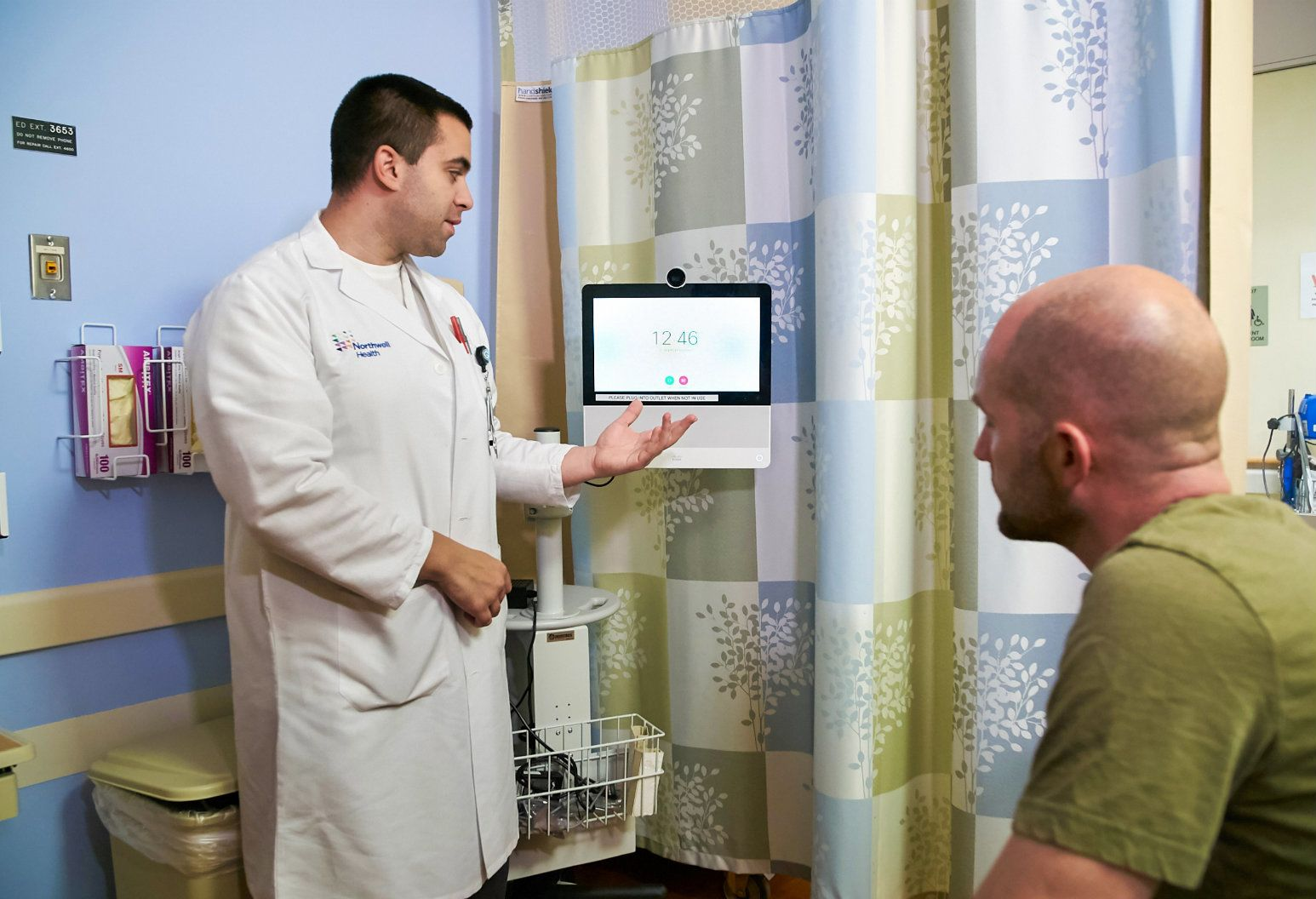 A health care employee explains TeleHealth technology to a behavioral health patient in a brightly-colored hospital room. The telehealth machine is a large tablet-sized screen with a camera mounted on a swiveling arm. Telehealth technology promises 24-hour access to care for patients wherever and whenever you need it.