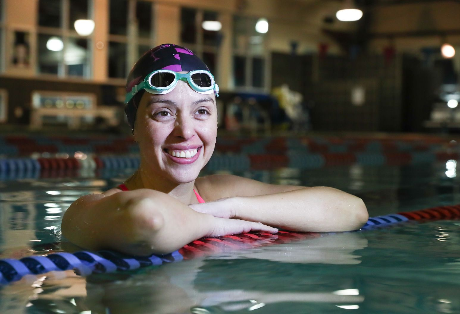 A 33-year-old woman in a pool rests her arms on the red and blue lane line. She smiles and looks off into the distance. She wears a purple swim cap and teal goggles resting above her eyes.