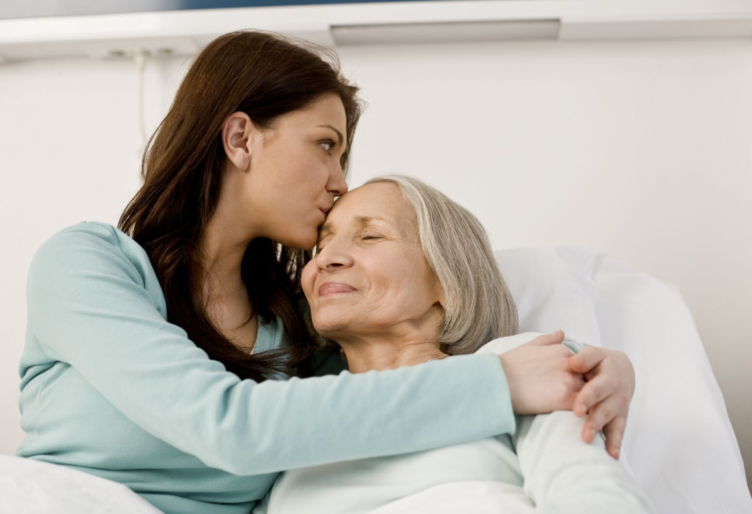 A young woman embracing an older woman who is lying in a hospital bed.
