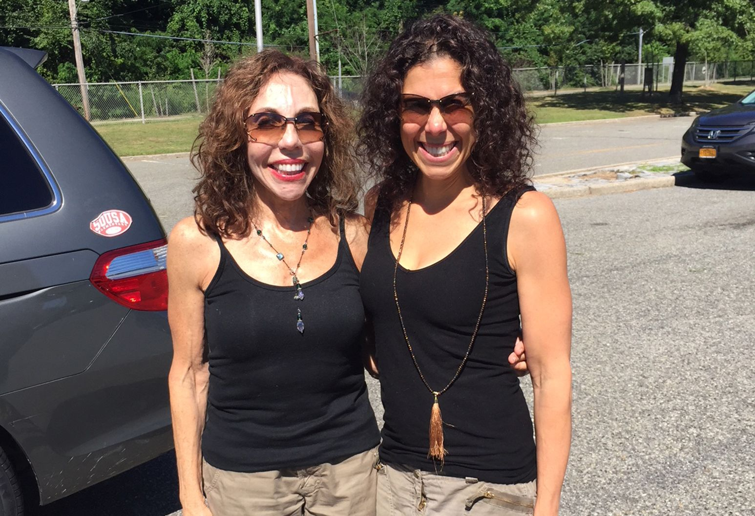 Two smiling women in matching outfits posing for a photo. They are wearing black tops, khaki bottoms, and their sunglasses have the same lens shade color.