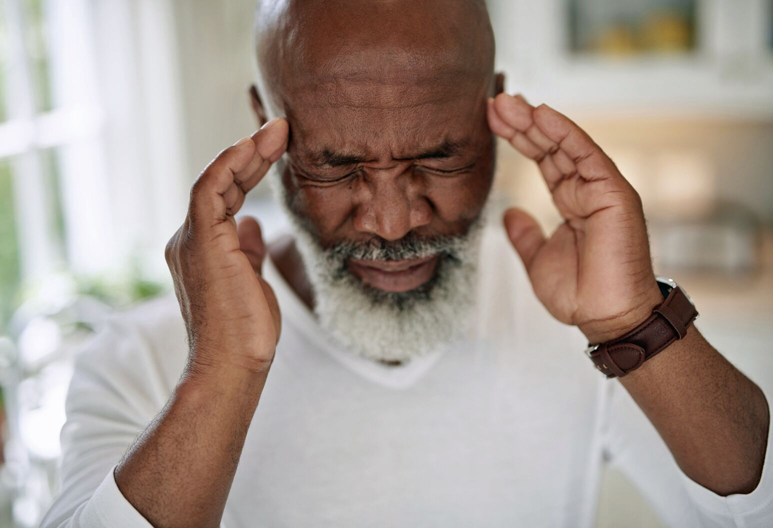 An elderly black man holds his head in pain