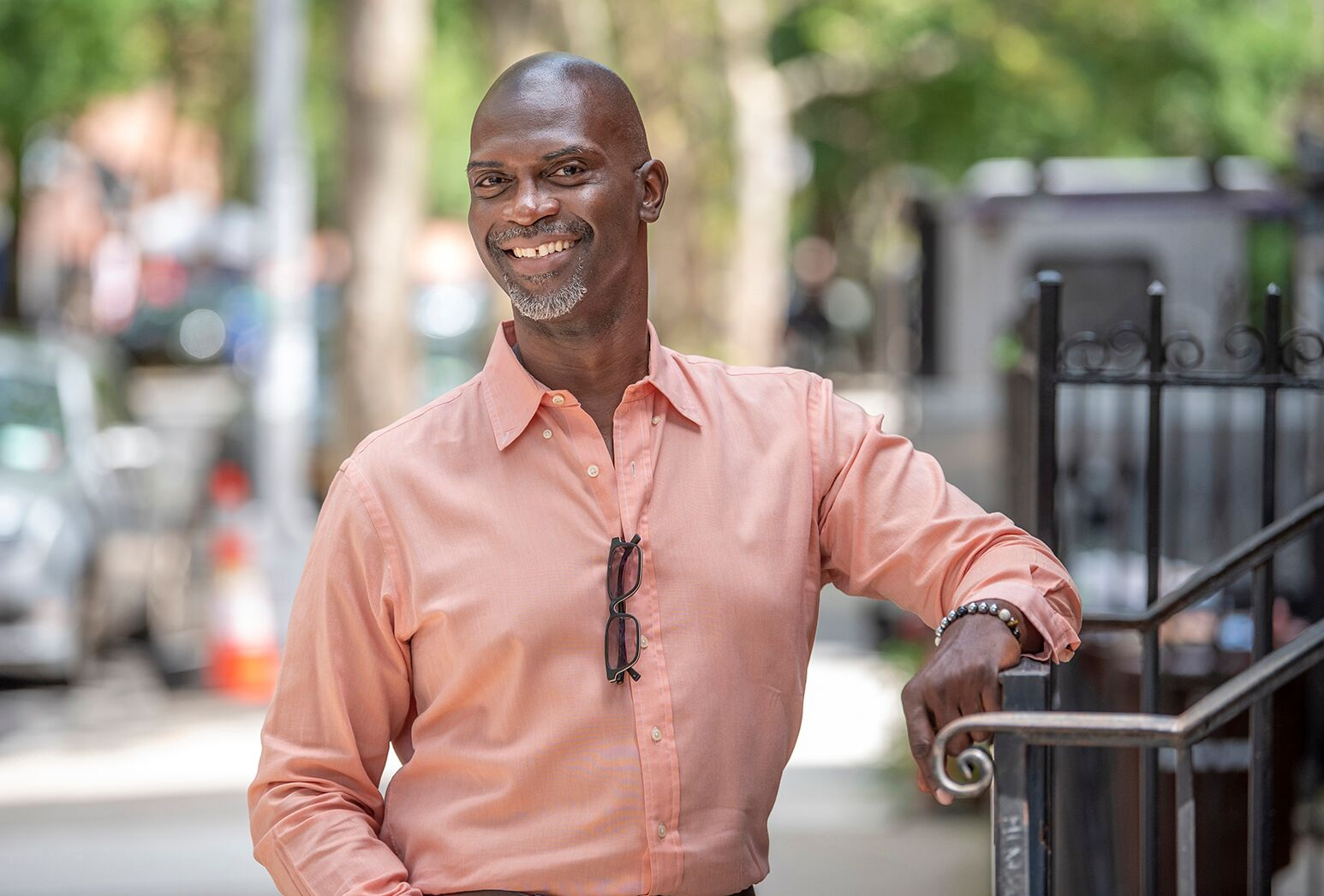 African American man in peach-colored, button-down shirt on a city street.