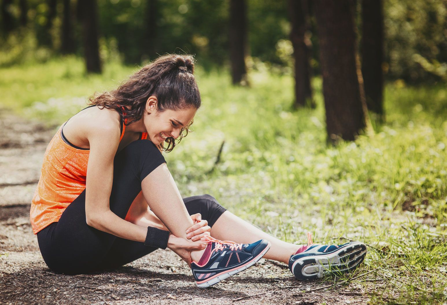 A young woman on a hike sits on the ground and holds her ankle in pain. Her brown hair is in a high pony tail and she's wearing an orange tank top, black leggings and sneakers. She's outside with grass and trees behind her.