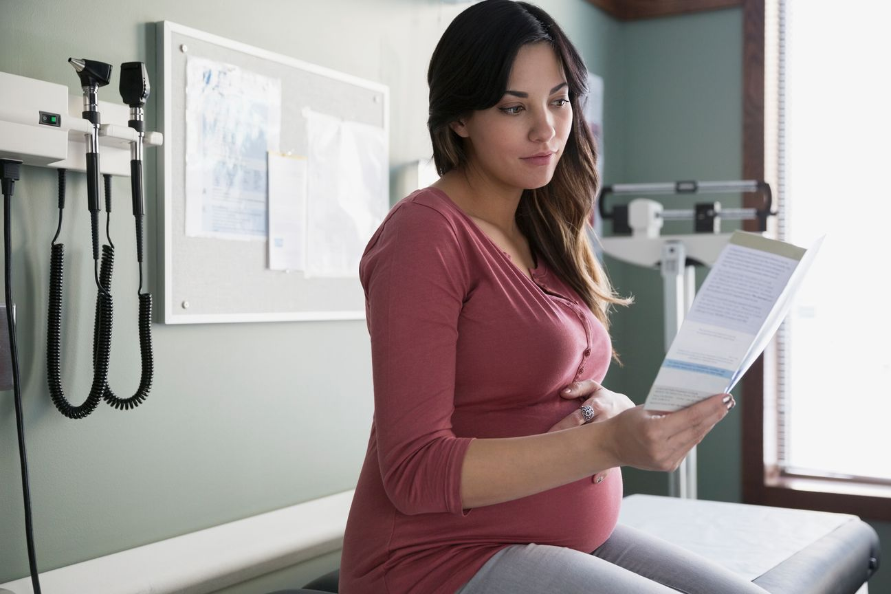 A pregnant woman holds her belly while reading a paper.
