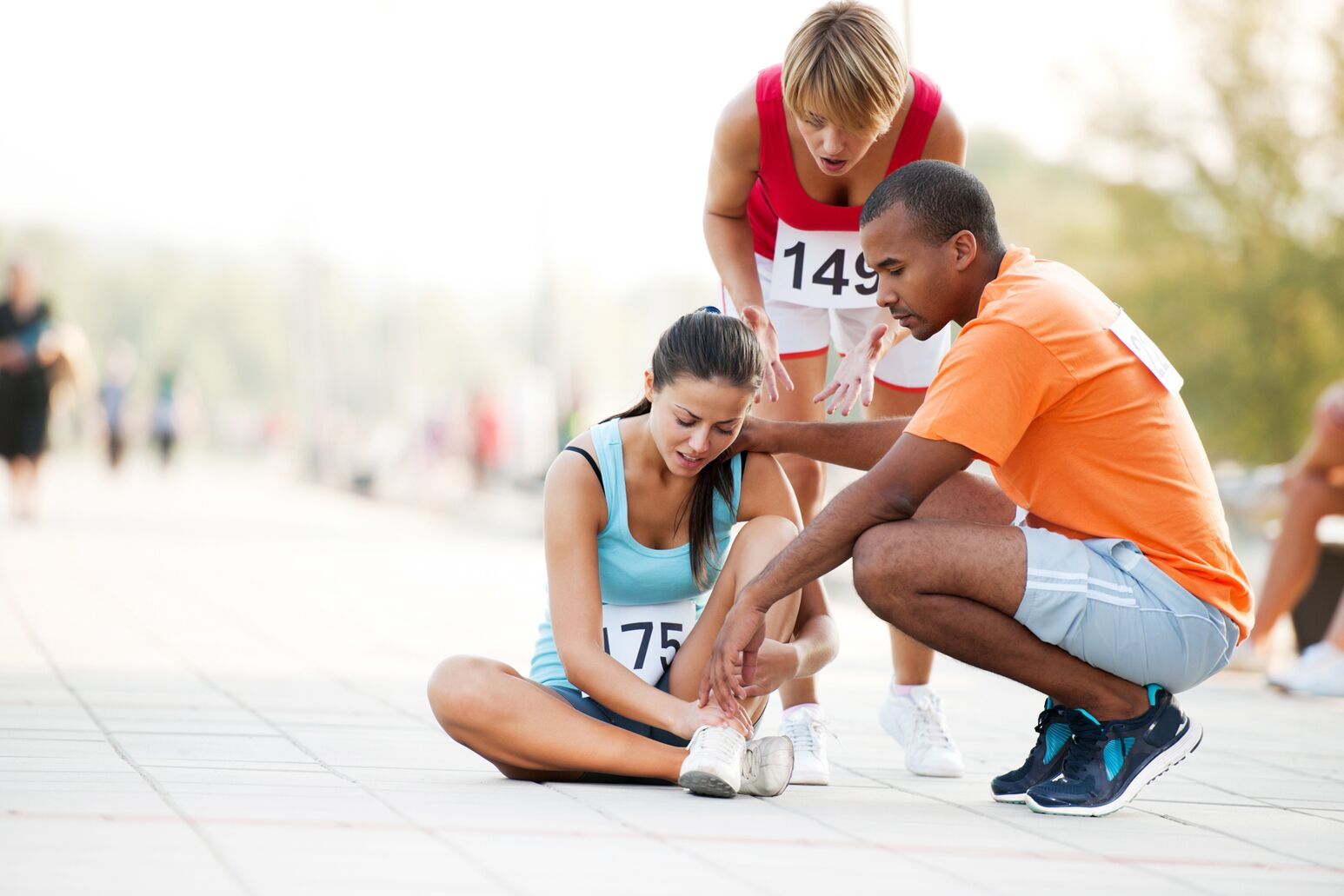 A female runner holds her ankle in pain with a black man and middle-aged woman looking to assist. Adam Bitterman, MD, highlights five ways you can prevent foot and ankle injuries.