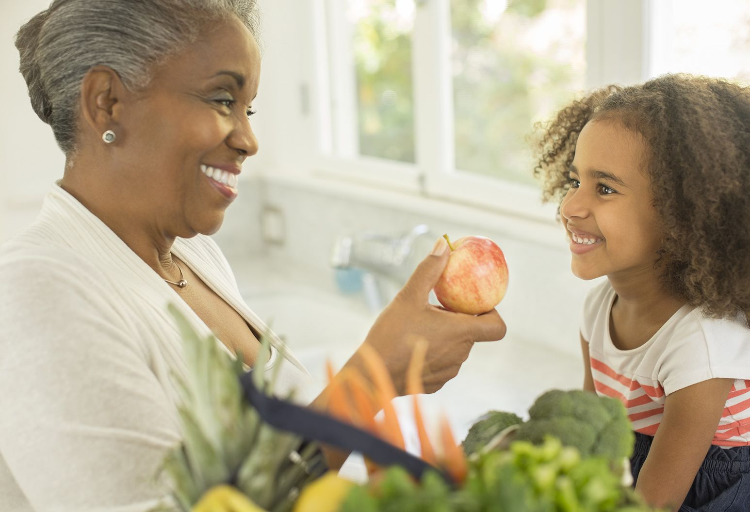 Happy grandmother giving apple to granddaughter in kitchen