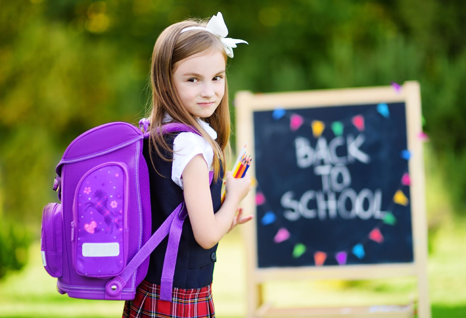 Young girl with purple backpack holding multi-colored pencils
