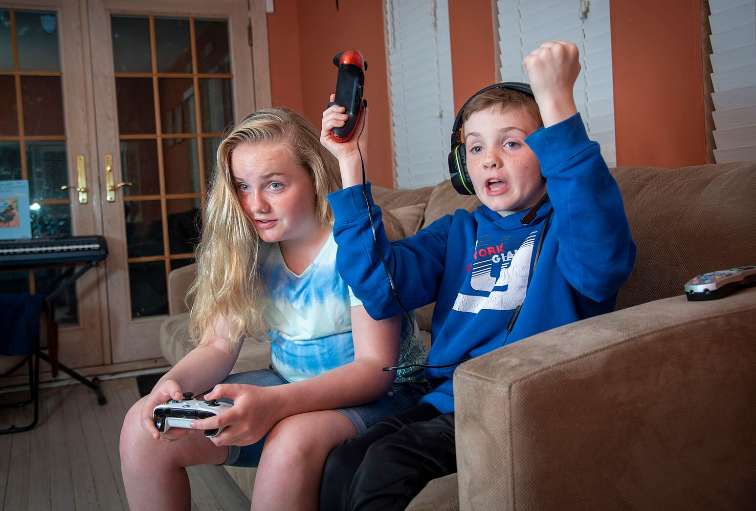 Young girl with long blond hair and boy with dark hair and headphones playing a video game on couch.