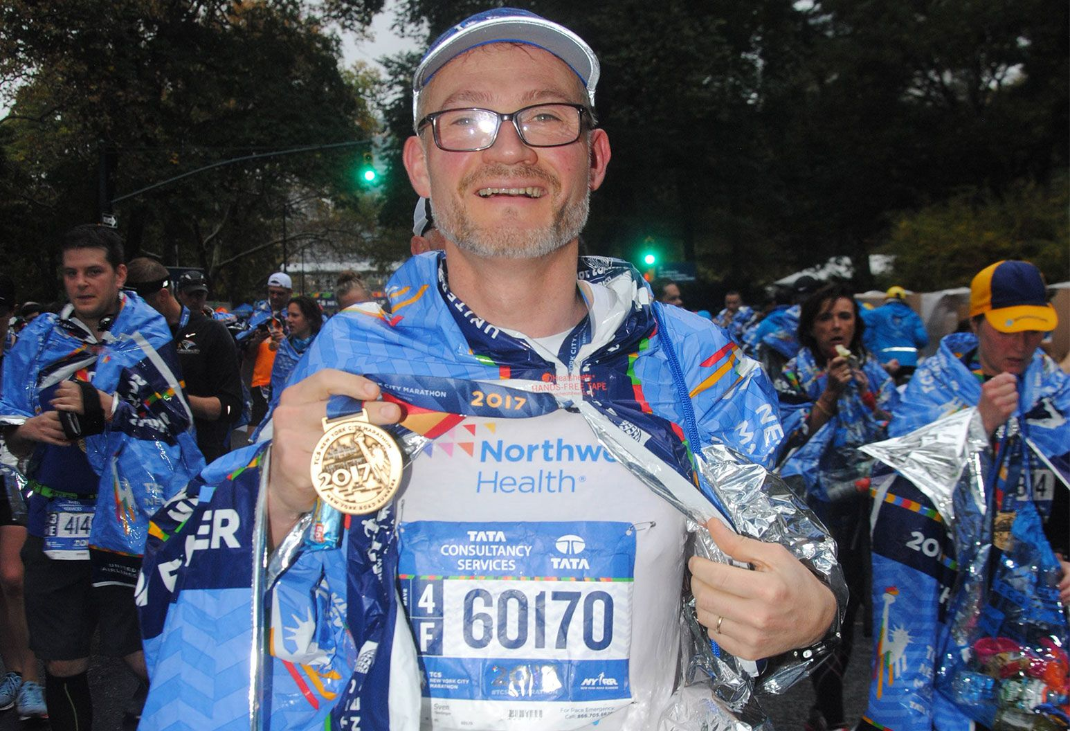 An older man in glasses with a scruffy beard stands exhausted holding a medal a gold medal in his right hand. He is wearing a running outfit with a marathon number attached to his shirt.