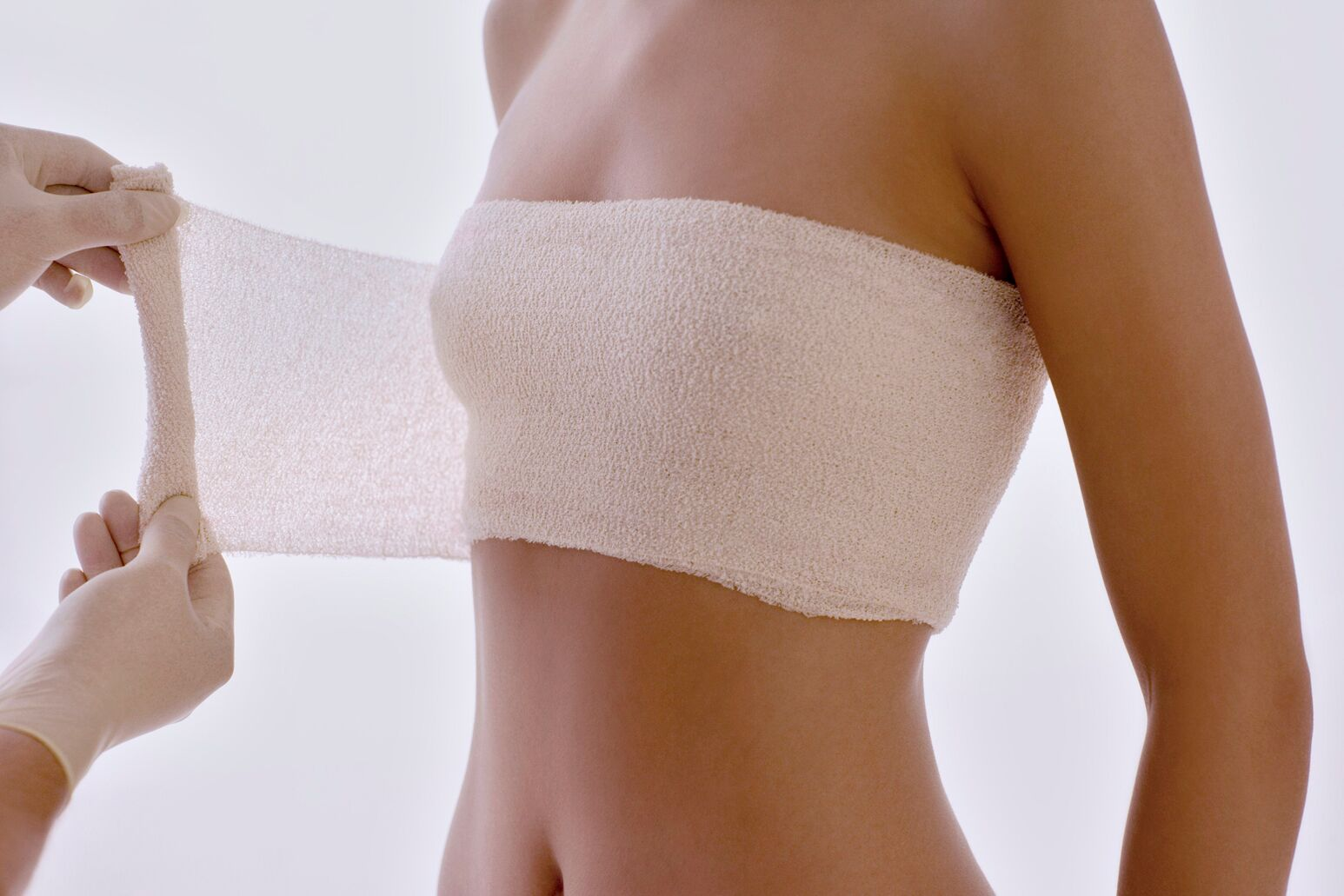 A doctor bandages a woman's breast