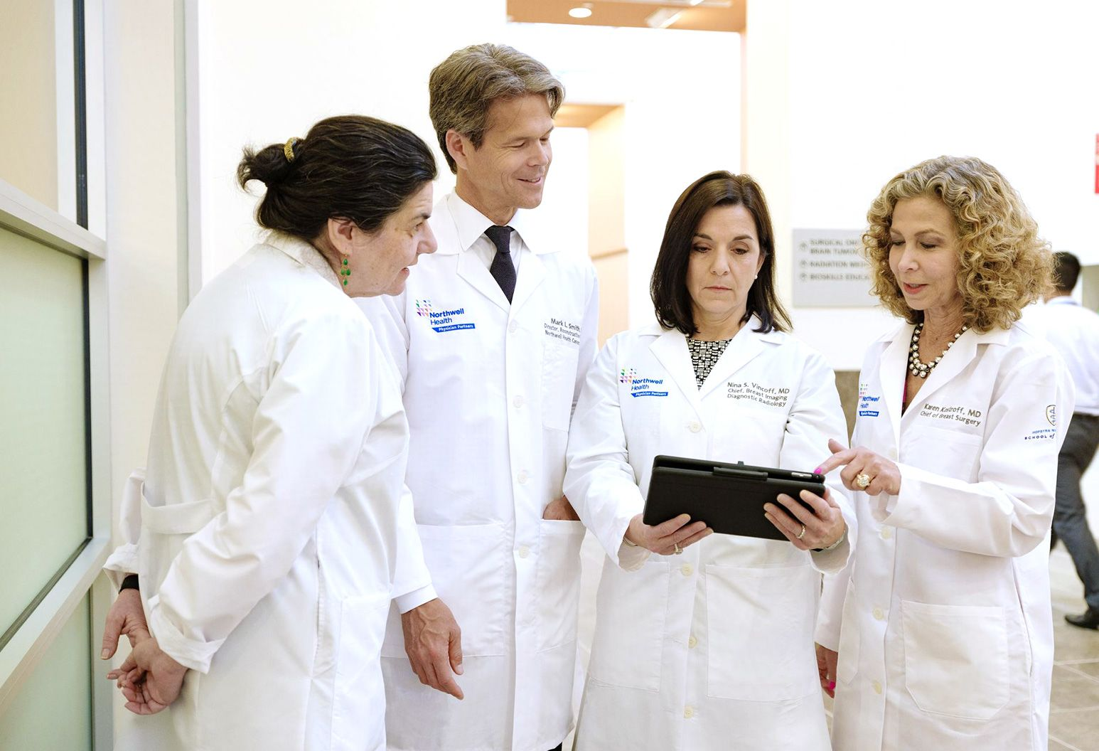 3 female doctors and 1 male doctor all wearing white lab coasts, stand together while looking at a patient chart.