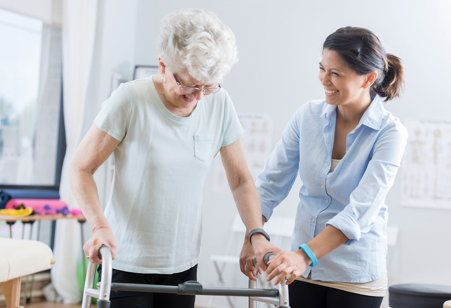 Cheerful senior Caucasian woman uses a walker during physical therapy session. A mid adult Asian female physical therapist is helping her walk with the walker.