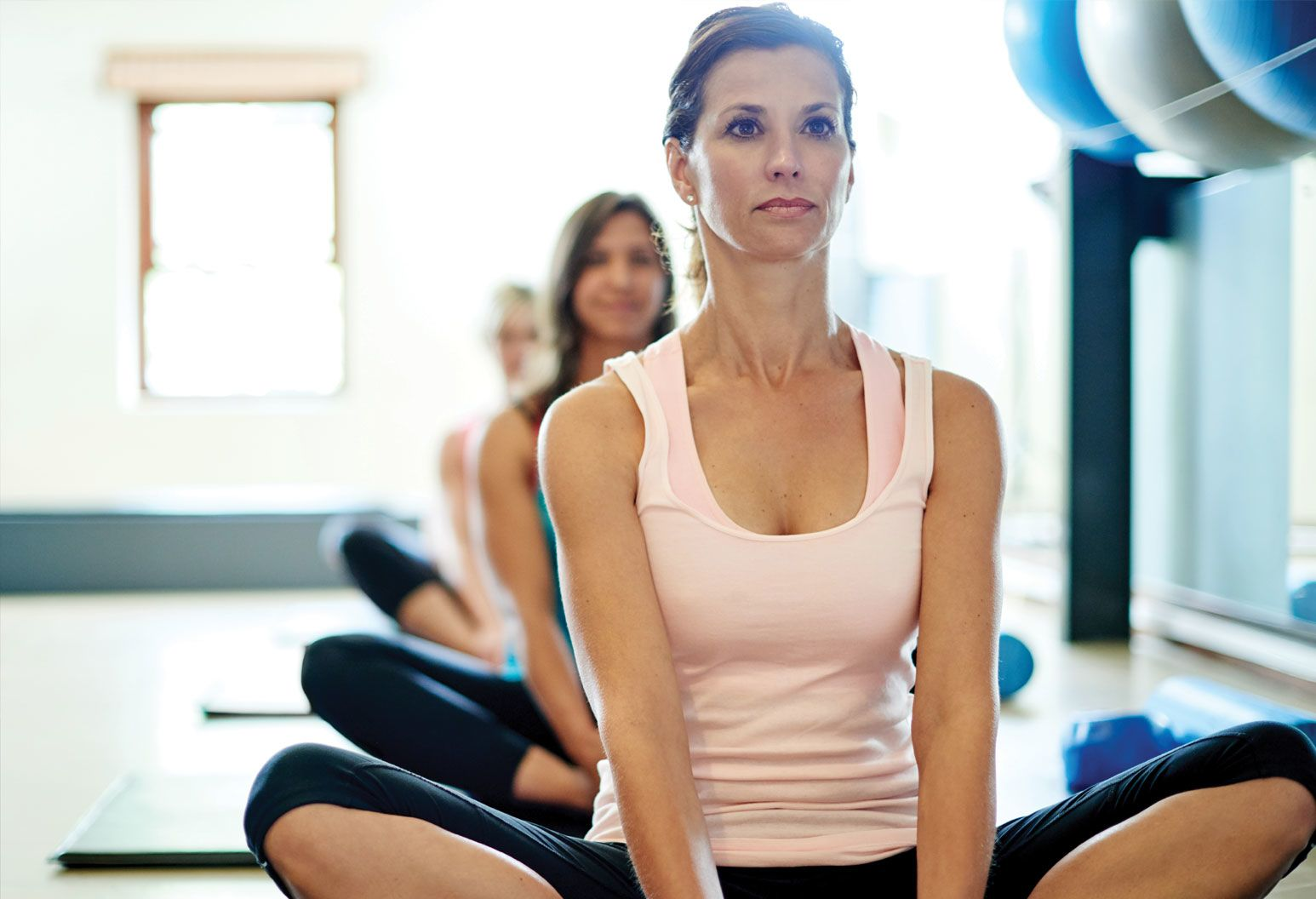 A group of women sit cross-legged in a workout class. The focus is on a woman in the front wearing a pink tank top and black knee-length leggings. The other women are blurred in the background. They all sit on yoga mats.