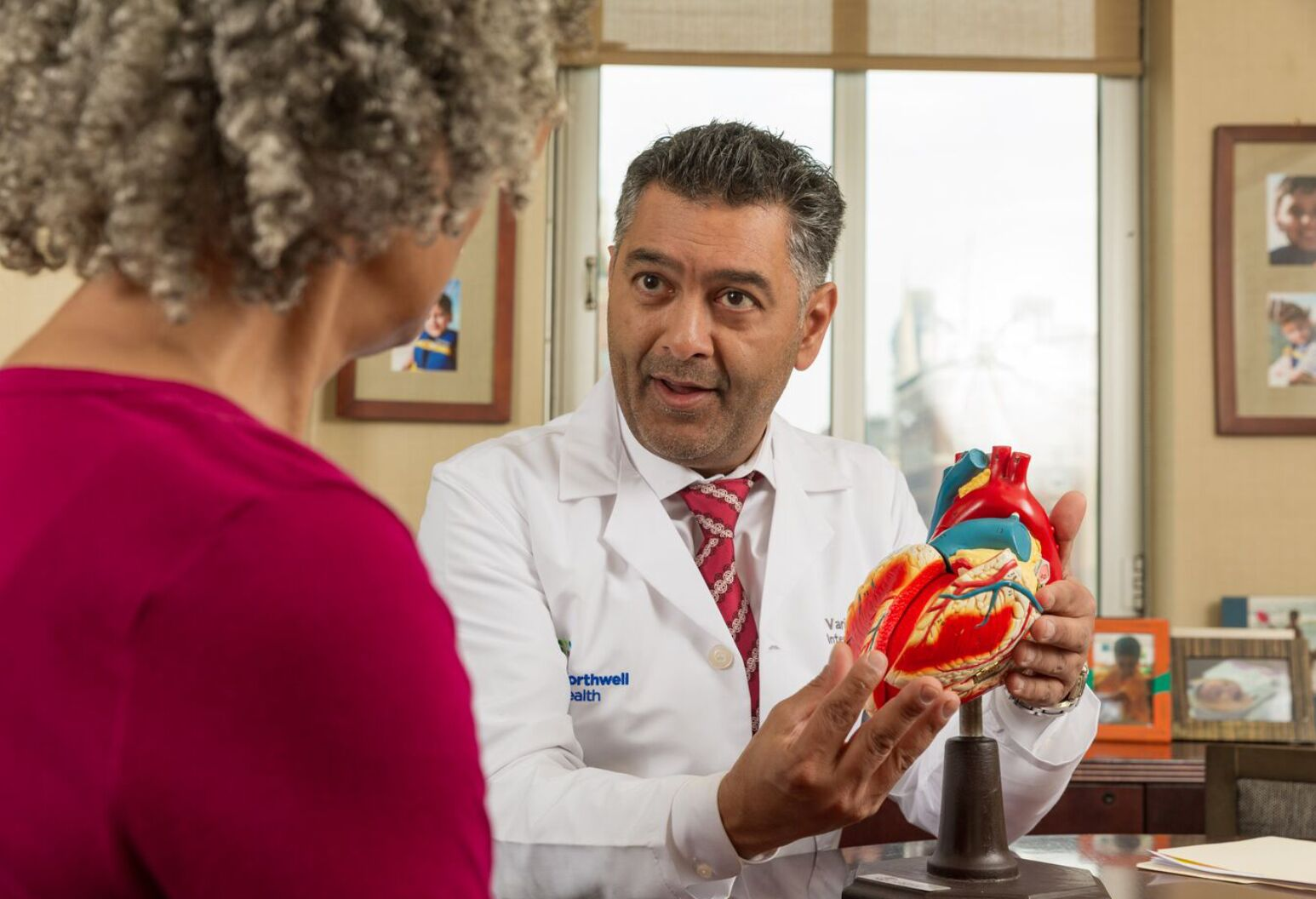 A doctor is talking with a patient. The doctor is holding a model heart.