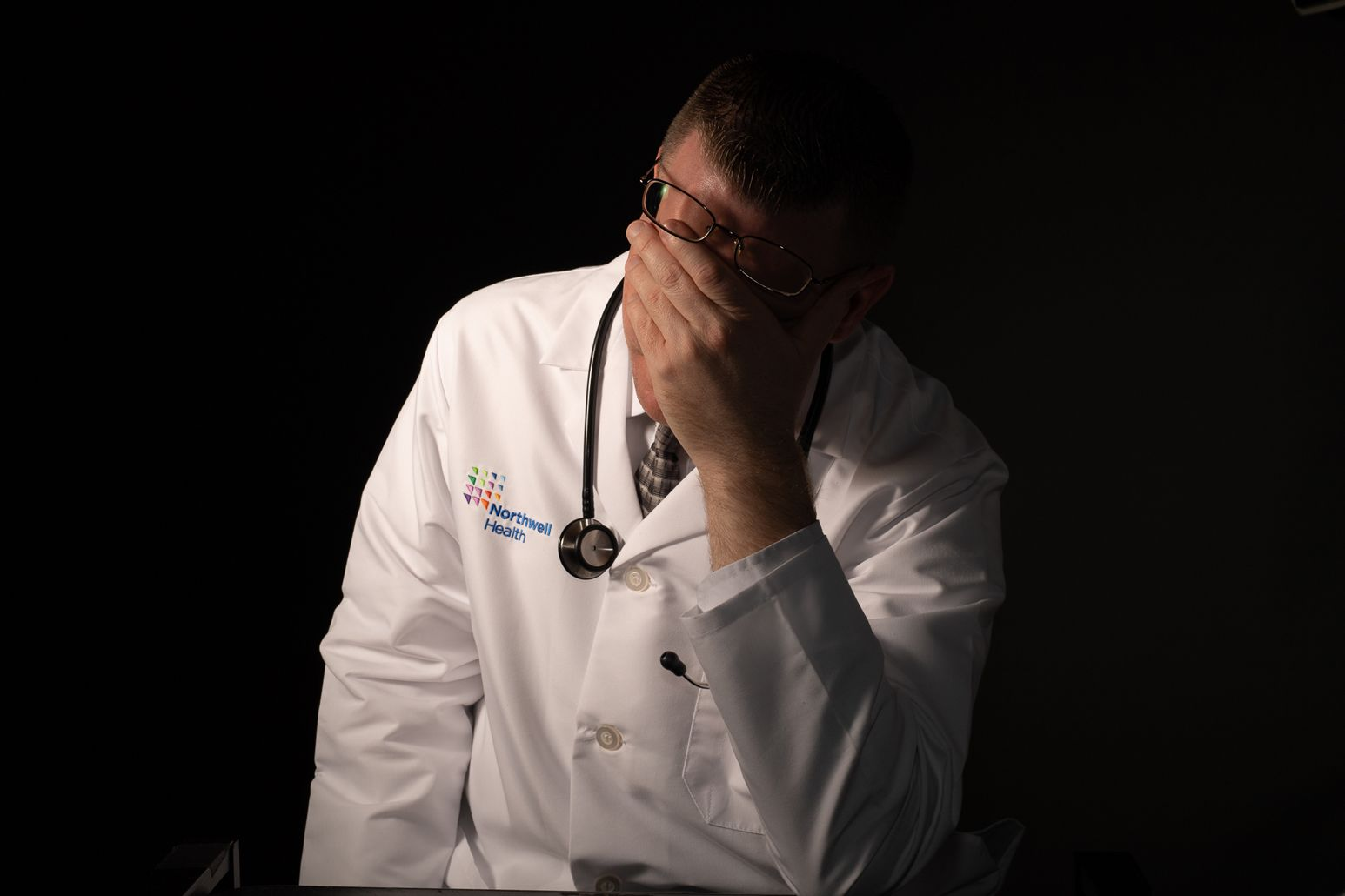 A stressed physician holds his head in his hand. Northwell has taken strides in opening communication and initiating programs to alleviate physician burnout.