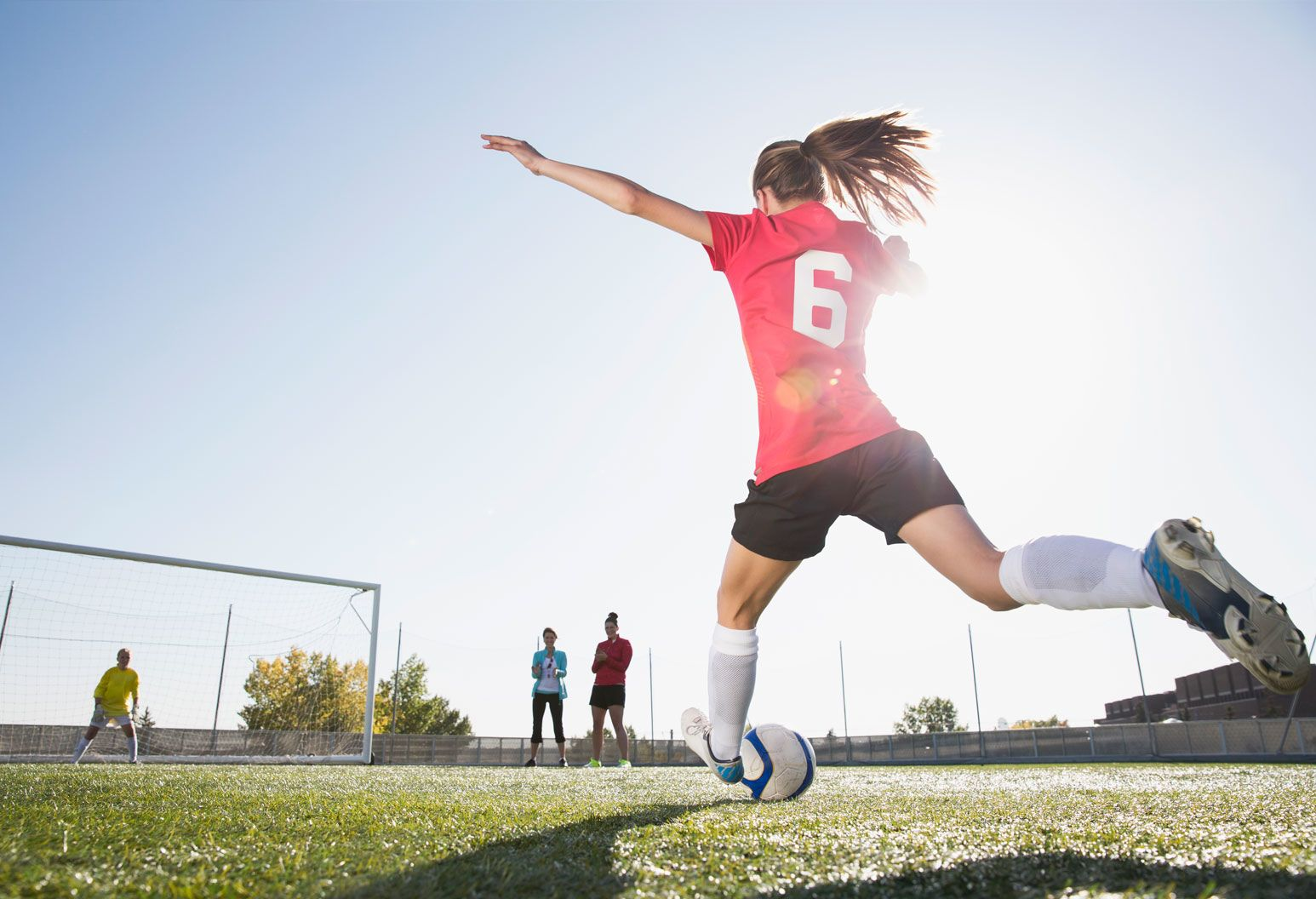 A young female soccer player is in motion to kick the ball into the soccer goal.